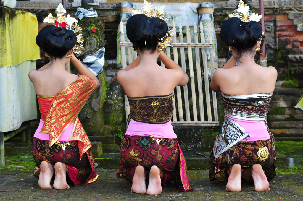 Bali girls pray at a temple during a festival