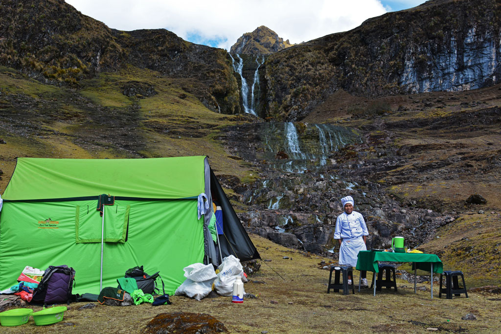 cook prepares lunch on lares trek with waterfall in background